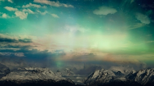 Surreal sky with glowing light and clouds over snow covered mountains.